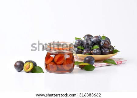 plate of fresh plums and jar of preserved plums on white background