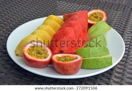 Plate of fresh tropical fruits on a white plate including Pineapple and Water Melon. - stock photo