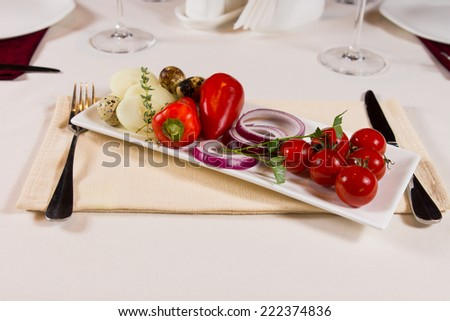 Plate of fresh vegetables as an accompaniment to a meal with red cherry tomatoes, sweet bell peppers, onion rings, mushrooms and herbs on a rectangular platter - stock photo
