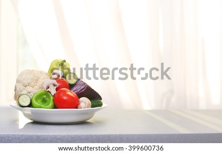 Plate of fresh vegetables on a table in front of window background - stock photo