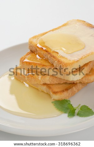 plate of freshly made toasts with butter and honey on white background