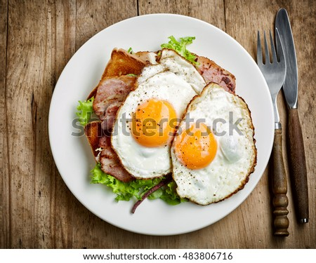 plate of fried eggs and bacon on white plate, top view