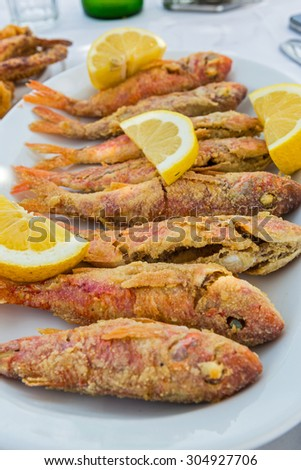 Plate of fried small fish red mullet and lemon - stock photo