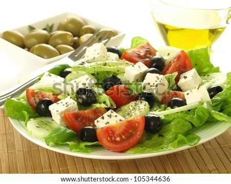 Plate of greek salad, glass of oil and olives - stock photo