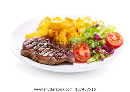 plate of grilled meat with vegetables on white background
