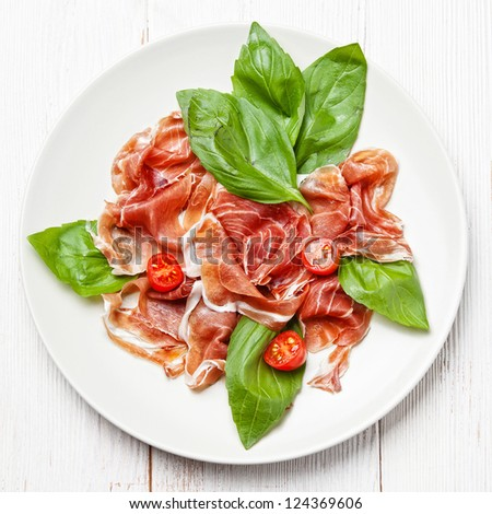 Plate of ham, tomato and basil