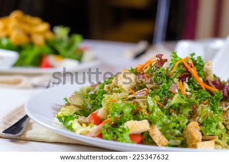 Plate of healthy leafy green mixed salad with golden fried crispy croutons with fresh lettuce, tomato, carrots and herbs - stock photo