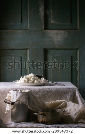Plate of homemade cottage cheese, served with vintage aluminum pan and water-can on white tablecloth with turquoise wooden background. Dark rustic atmosphere.  - stock photo