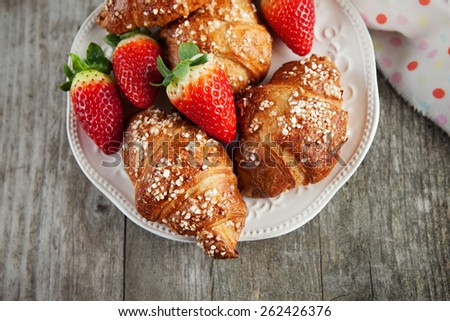 Plate of homemade croissants and fresh strawberries on old wooden background, selective focus