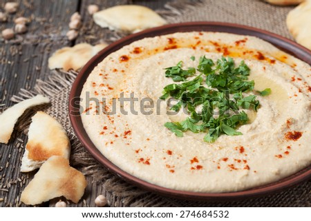 Plate of hummus, healthy lebanese traditional creamy food with chick-peas, tahini and pita flatbread on vintage wooden background - stock photo
