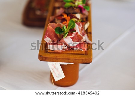 Plate of Italian Appetizer brusquest on wooden desk on the table.Italian antipasti, jamon, prosciutto, chorizo, salami on a grunge black board, rustic style. Selective focus. - stock photo