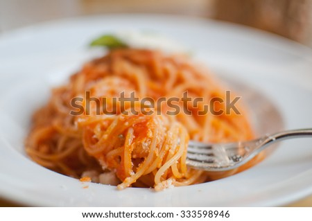 Plate of Italian pasta (spaghetti) with tomato and basil on street cafe table - stock photo