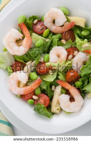Plate of Italian shrimp salad with shrimp, tomatoes, artishocke hearts, Romane lettuce leaves, fava beans, and pine nuts. Olive oil.  - stock photo
