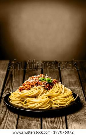 Plate of Italian spaghetti Bolognese topped with ground beef and basil and sprinkled with parmesan cheese on a rustic wooden table with copyspace - stock photo