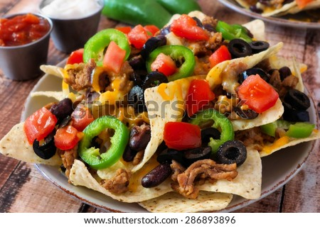 Plate of Mexican nachos loaded with ground meat, jalapenos, tomatoes, beans and melted cheese - stock photo