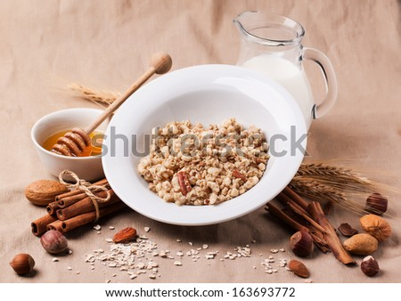 Plate of muesli with milk, honey, cinnamon and nuts over textile background