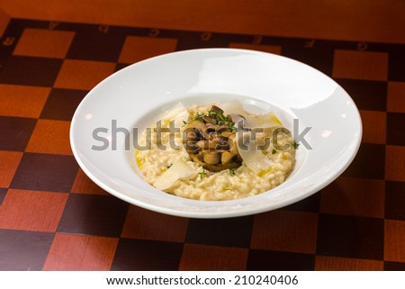 Plate of mushroom risotto with parmesan on the table - stock photo