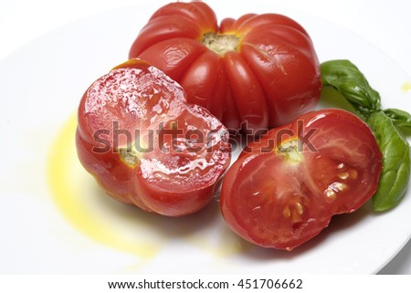 plate of organic tomato with olive oil and chopped basil