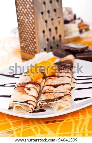 plate of pancakes decorated with orange peel and syrup