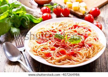 plate of pasta with tomato sauce on wooden table - stock photo