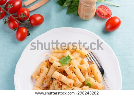 Plate of penne pasta with bread crumbs, basil and cherry tomatoes on blue tablecloth. - stock photo