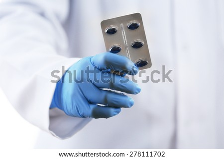 Plate of pills in doctor hand on white background - stock photo
