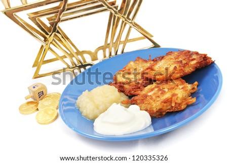 Plate of potato pancakes, a dreidel and Hanukkah gelt, and a menorah on white. - stock photo