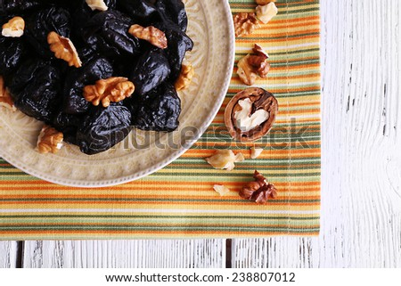 Plate of prunes and walnut on striped napkin with shell on color wooden background - stock photo