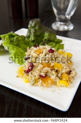 Plate of quinoa salad with dried fruit and pumpkin seeds - stock photo