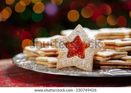 Plate of raspberry jam sandwich sugar Christmas cookies in star shaped cutout under the Christmas tree with defocused lights - stock photo