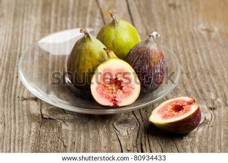 Plate of Ripe Fig Fruits on old wooden table - stock photo