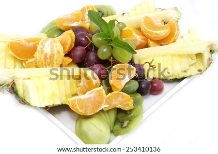 plate of ripe juicy fruit on white background - stock photo
