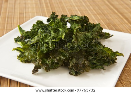 Plate of roasted kale chips on a bamboo matt - stock photo