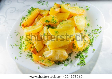 Plate of roasted potatoes. - stock photo