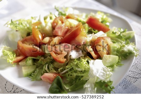 Plate of salad with tomato, lettuce, cucumber and some dried fruit.