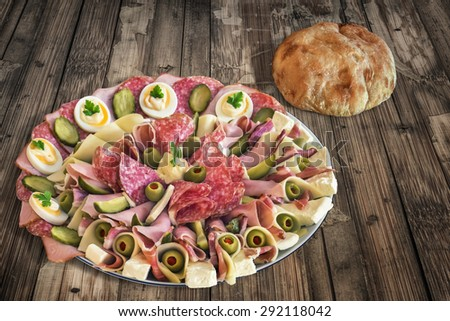 Plate of Serbian Meze with domestic Pita Bread loaf, placed on very old, weathered, cracked, scratched, peeled off, Wooden Table. - stock photo