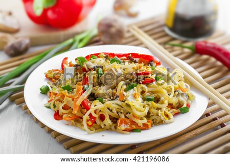 Plate of stirred rice noodles with tofu, vegetables and shiitake on a table. Traditional Asian cuisine meal.