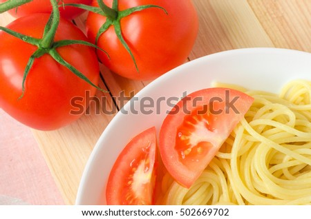 plate of tasty pasta with cut tomato and whole tomatoes at background