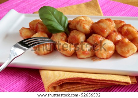 Plate of tomato sauce gnocchi on yellow napkin and pink place mat ...
