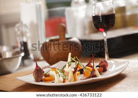 Plate of vegetable salad and wine on a kitchen table