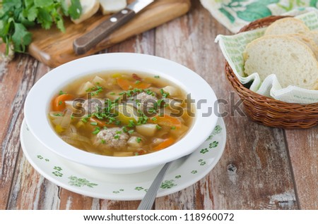 Plate of vegetable soup with meatballs on the wooden table