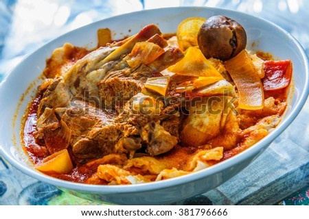 Plate of yellow rice topped with mutton meat and potato. - stock photo