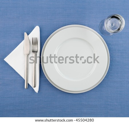 plate on blue tablecloth - stock photo
