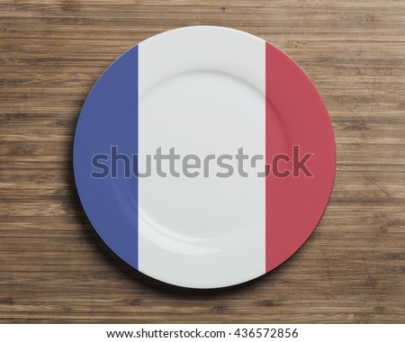 Plate on table with overlay flag of France - stock photo
