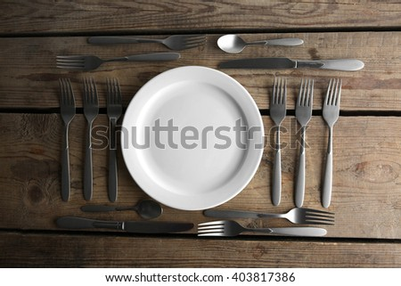 Plate, silver forks and knives on wooden table, top view - stock photo