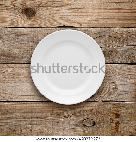 Plate top view on old wooden table - stock photo