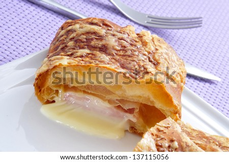 plate with a ham and cheese croissant on a set table with a purple tablecloth