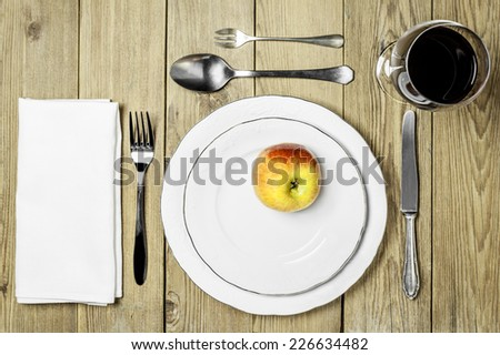 Plate with an apple, cutlery set, a napkin dining room and wine glass on a wooden background - stock photo