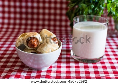 Plate with artisan mini hot dogs (Sausage in the dough) and a glass of fresh cow's milk with parsley on a plaid background. On July 18, America celebrates the Day of Hot Dog. - stock photo
