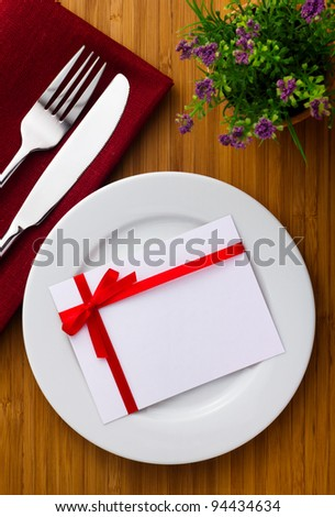 Plate with card with red bow on wood table - stock photo